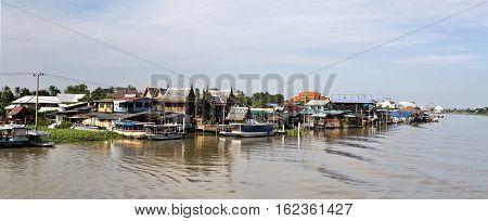 BANGKOK, THAILAND - November 4, 2016: Modest living styles with houses on stilts along the banks of the Chao Phraya River in Bangkok Thailand