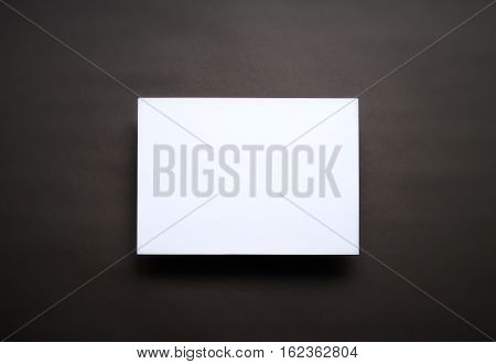 Empty white paper sheet isolated on dark brown background