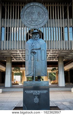 Statue of Father Damien in fromt of the Hawaiian State Capitol building in downtown Honolulu