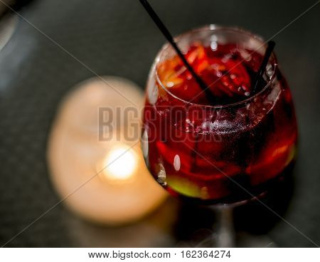Red wine fresh tasty sangria cocktail drink. beautiful blurred background and candle light on black table outside