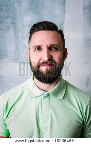 Portrait of young adult bearded happy man looking at camera