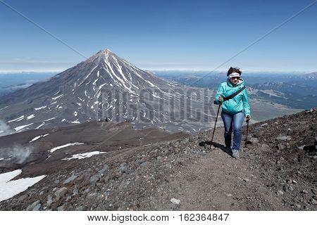 AVACHA VOLCANO KAMCHATKA PENINSULA RUSSIA - AUGUST 07 2014: Hiking on Kamchatka - woman tourist climbing to top of Avachinsky Volcano on background of Koryaksky Volcano in sunny weather.