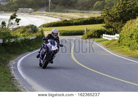 Falmouth Massachusetts USA - October 3 2008: Motorcyclist negotiating curves near Nobska Point Lighthouse