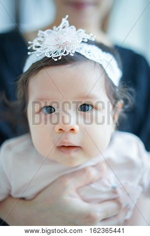 Sweet Beautiful baby girl with hug of mom Joyful Happy Excited. Closeup Headshot