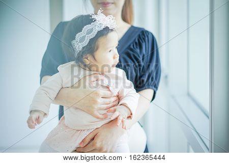 Sweet Beautiful baby girl with hug of mom Joyful Happy Excited. Closeup Headshot