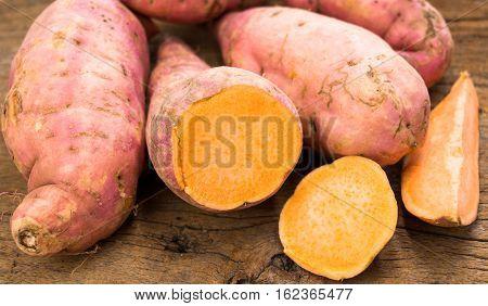 fresh cut orange sweet potatoes on wooden table