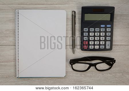 A blank notebook with a pencil and a calculator on a grey wooden background