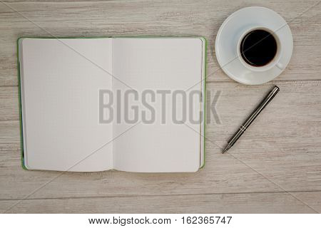 A blank notebook with a pencil and a cofee on a grey wooden background