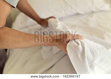 closeup of a young man extending the bedsheet or the duvet on the mattress as he is making the bed