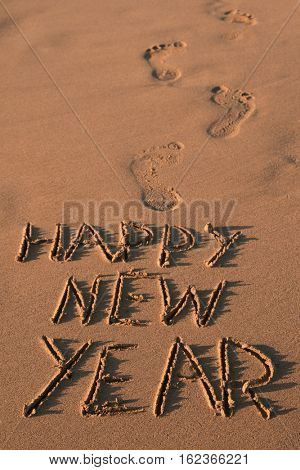 some foot prints and the text happy new year written in the sand of a beach