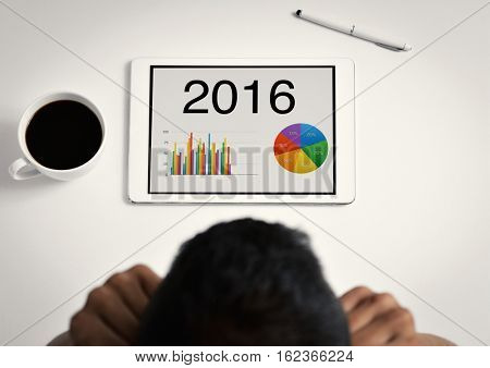 closeup of a concerned young caucasian businessman sitting at his office desk with his hands in his head, observing the economical balance of the year 2016 in his tablet computer