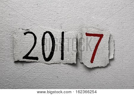 the number 2017, as the new year, handwritten in some pieces of rustic paper in black and red, placed on a background of the same rustic paper