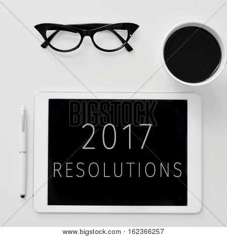 high-angle shot of a tablet with the text 2017 resolutions in its screen, a pair of womens eyeglasses, a pen and a cup of coffee, on an off-white surface