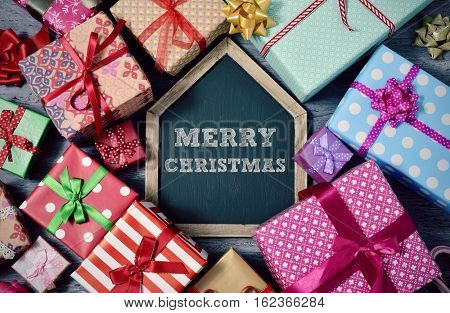 high-angle shot of a pile of gifts wrapped in nice papers and tied with ribbons, and a house-shaped chalkboard with the text merry christmas written in it, on a rustic wooden surface