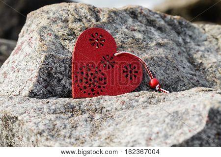 Red wooden heart simbol lying on stone.