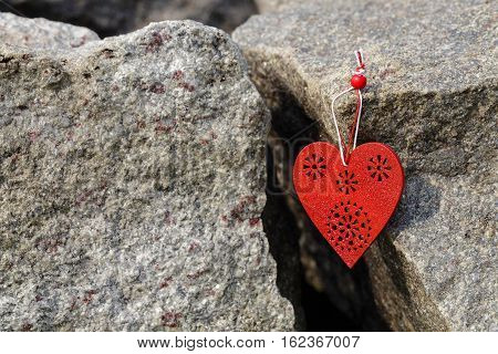 Red wooden heart symbol hanging on big stone. Love concept.