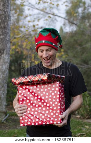 Man surprised by Christmas gifts he is holding outside.