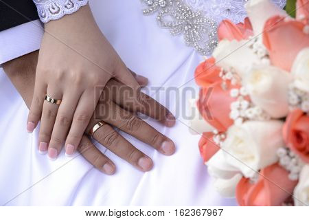 Wedding rings and bouquet white and melon