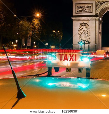 illuminated taxi sign of a Parisian taxi at night with the Arc de Triomphe in the backround