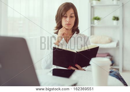 businesswoman with laptop and diary in a bright office concept freelance work at home