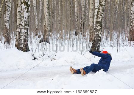 Young stylishly dressed people during a walk on a birch grove fell on a slippery road and trying to climb