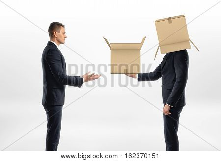 Businessman with a cardboard box on his head passed another box to another man, on white background. Business world. Communication at work. Fitting in.