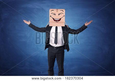 Businessman raising his hands up and wearing a box on his head with a laughing face painted on it. Business success. Hidden emotions. Favourite job.
