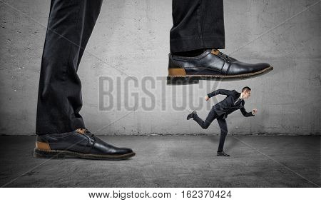 A businessman is running away from a big foot on a gray concrete background. Suppression of competitors. Big business.