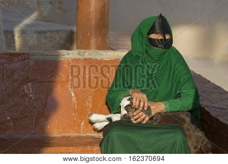 Nizwa Oman December 15th 2016: Omani woman with a baby goat the the market