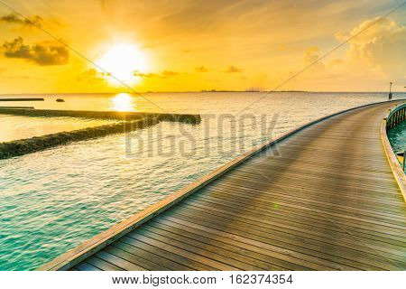 Beautiful water villas in tropical Maldives island at the sunrise time