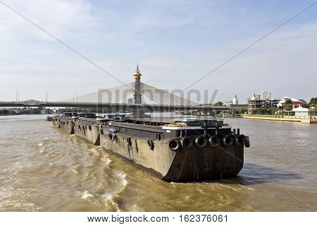 Huge empty cargo barges being towed upstream the Chao Phraya River in Bangkok Thailand