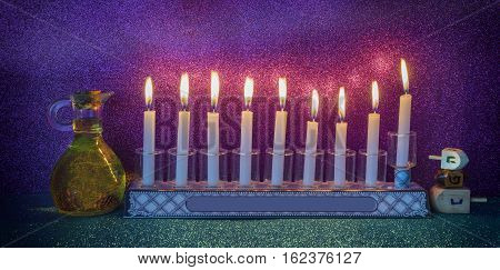 Jewish menorah with candles, jar of olive oil and wooden dreidels are traditional symbols for Hanukkah Holiday