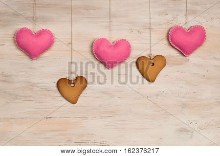 Cookies in heart shape and pink felted heart hanging over wooden background place for text