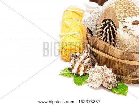 Peeling and spa accessories in wooden basket, towel and skin care products on white background. Copy space