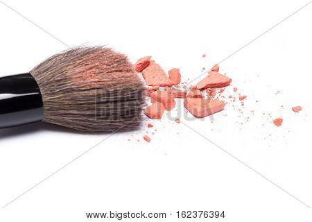 Crushed compact blush apricot color with makeup brush on white background. Shallow depth of field