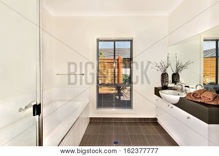 Luxurious bathroom of a modern house or hotel including white and long bath tub next to the countertop which is dark gray color and a white washstand with a silver faucet fixed to it front of the big and wide mirror.