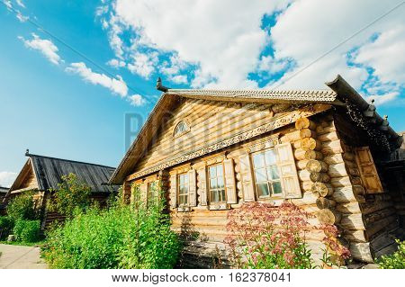Wooden hut Slavic type on a summer day against the blue bright sky with clouds