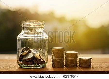 Saving money for prepare concept Rows of coins with account for finance and banking concept Glass bottle with money coin stack growing business