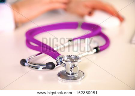 Stethoscope in the foreground, in the background arms.