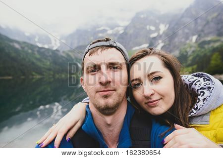 Happpy couple taking selfie withe lake background in the mountains