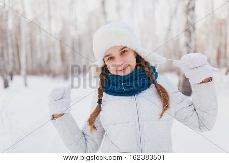 Cute teen girl smiling in winter park. Girl in a white hat with ear flaps and blue scarf laughs