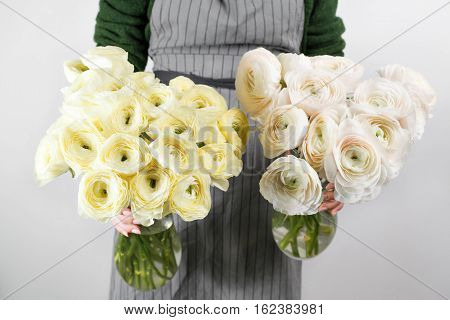 Beautiful bouquet of soft lemon and white ranunculus in woman's hands, mother's day concept.