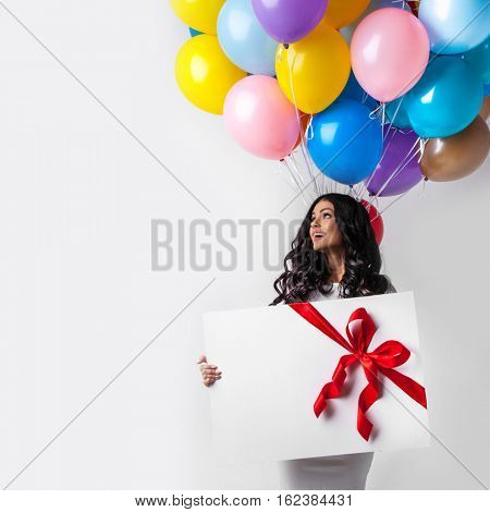 Young smiling woman with balloons and big gift box