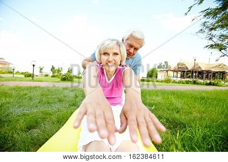 Senior woman doing forward bend with husband s assistance