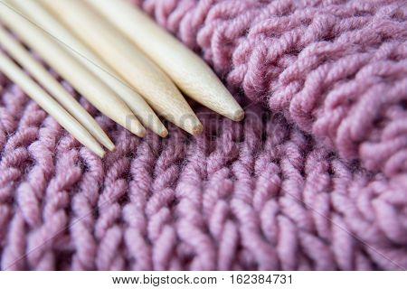 Different size knitting bamboo spokes and pink knitted wool fabric close up, selective focus