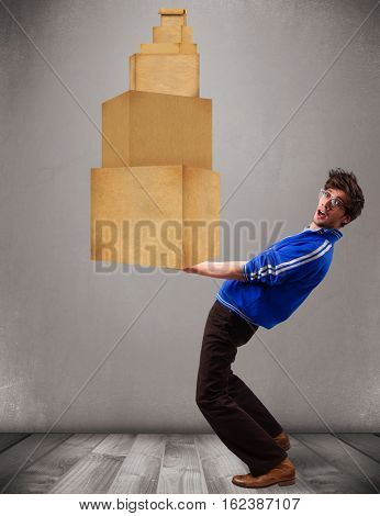 Handsome young man holding a set of brown cardboard boxes