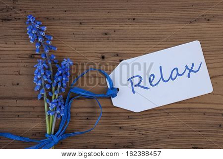Label With English Text Relax. Blue Spring Grape Hyacinth With Ribbon. Aged, Rustic Wodden Background. Greeting Card For Spring Season
