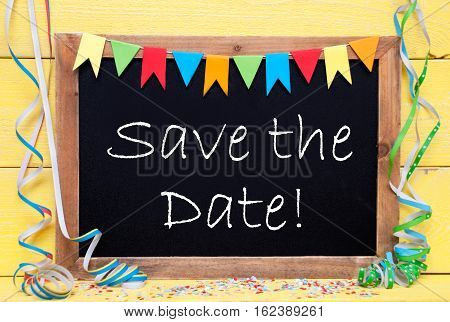 Blackboard With English Text Save The Date. Party Decoration Like Streamer And Confetti. Yellow Wooden Background. Greeting Card For Celebrations