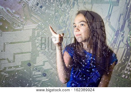 11 year girl pointing her finger to the silhouette of a computer motherboard at the Informatics lesson in school. copy space for your text inscription.