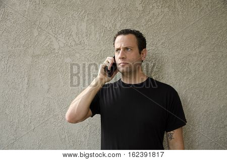 Man having a concerning phone call on his smart phone.